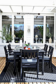 Set table and black chairs on roofed terrace