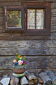 Autumnal flower arrangement in sapucaia nut shell outside rustic wooden house