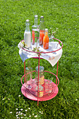 Bottles of soft drinks and delicate cherry blossom on round side table in garden