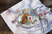 Pastries and petit four on plate on handmade place mat with cherry blossom motif