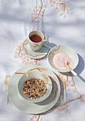 DIY-Tischdecke und Frühstücksgeschirr mit Kirschblütenmotiv, Tee, Joghurt und Müsli