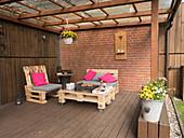 Sitzgruppe aus Palettenmöbeln auf überdachter Terrasse