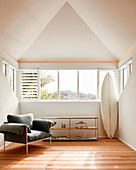 Designer armchair, shelf and surfboard in a bright room with a pointed roof