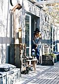 Holzterrasse mit Ofen, Frau steht an der Tür