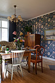 Various old furnishings and blue wallpaper in dining room