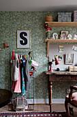 Kleiderständer und alter Schreibtisch vor grüner Tapete