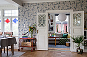 Open double doors painted white, vintage serving trolley and house plants against patterned wallpaper