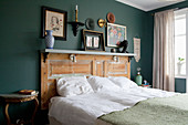Double bed with headboard made from old door in bedroom with green walls