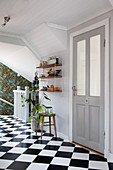 White wood panelling and chequered floor in bright hallway