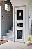 Door with chalkboard panels next to foot of staircase in foyer