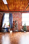 Frau am Tisch vor Fenster, daneben Leiter mit Weihnachtsdekoration, Rehfigur und kleiner Tannenbaum vor Backsteinwand