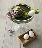 Unfertiges Blumenarrangement mit Artischocke und Eiern zu Ostern