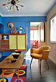 Keramikschalen auf Couchtisch, Polstersessel und Highboard im Wohnzimmer mit blauer Wand