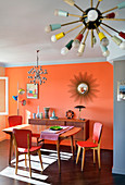 Dining area and sideboard in retro interior with orange wall