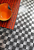 Orange bowl on bench on black-and-white mosaic floor