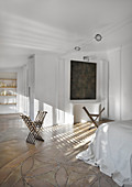 X-chairs in white bedroom flooded with sunlight
