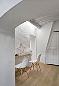 Shell chairs at narrow desk below skylight