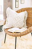 Cushion with macrame cover on wicker chair