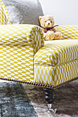 Teddy bear sitting on armchair with yellow and white graphic pattern on cover