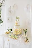 Buffet mit Hochzeitstorte, weiße Papierdeko an der Wand