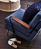 Upholstered blue armchair with pillows
