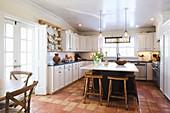 Holzstühle an der Kücheninsel in amerikanischer Landhausküche