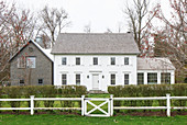 Fence and hedge surrounding American farmhouse