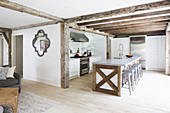 Rustic wooden beams in open-plan interior with island counter in open-plan kitchen