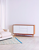 Retro sideboard and upholstered sofa against white wall
