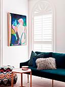 Sofa mit Kissen, Beistelltisch und Sitzpouf vor Rundbogenfenster und Kunstwerk