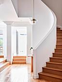 Holz-Wendeltreppe und weiße Wände im Treppenhaus