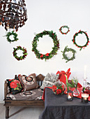 Wreaths of various sizes above bench with cushions