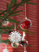 Red rose in glass Christmas-tree bauble and paper decoration