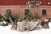 Table set for Christmas below metal wreaths outside brick house