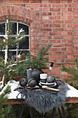 Tisch mit schwarzer Weihnachtsdeko und Tannenzweigen vor Backsteinhaus