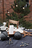 Black Christmas decorations and candle on table outside brick house