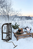 Crockery on rustic wooden table, Christmas decorations and wooden sledge in snowy landscape
