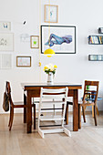 Yellow pendant lamp providing splash of colour above square dining table and wooden Tripp Trapp chair