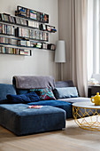 Grey-blue sofa below wall-mounted shelves in corner of living room