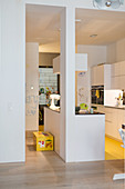 White kitchen furnishings and bright yellow floor in open-plan kitchen area