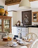 Vintage, französisches Schild über Herd in rustikaler Küche, Teegeschirr und Kuchen auf Tisch