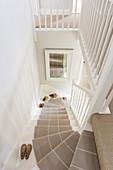 Weißes Treppenhaus mit beigem Treppenläufer, antike Schuhleisten auf Treppe
