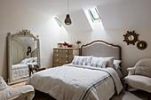 Verzierter französischer Spiegel und Doppelbett im Gästezimmer mit Dachschräge