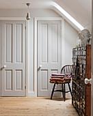Antiker Apothekerschrank und Windsor-Stuhl im Zimmer mit Holzdielen