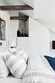 Weißes Schlafzimmer mit Doppelbett, darüber rustikale Holzbalken