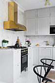Pale grey fitted kitchen with marble splashback and brass extractor hood