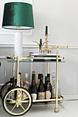 Table lamp and drinks on brass serving trolley against pale grey wall