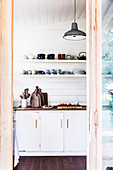 Glance into kitchen with white base cabinet and wall boards