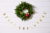 Christmas wreath and 'Merry Christmas' inscription on white wooden wall