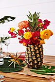 Bouquet of flowers in pineapple vase on table decorated for Christmas